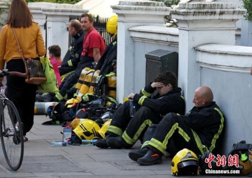 图2 6月14日,伦敦西部一栋高层的公寓楼发生大火,火势猛烈,蔓延到了所有楼层。图为疲惫的消防员在路边休息。