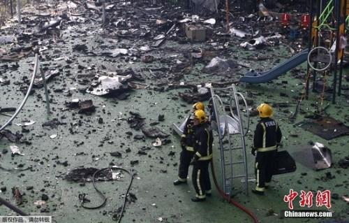 图为消防员在瓦砾中行进。