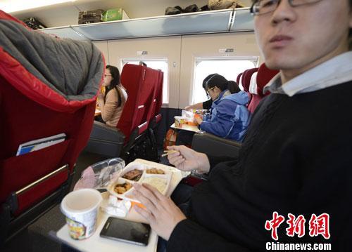 资料图:图为动车组乘客在品尝列车提供的餐食。<a target='_blank' href='http://www.chinanews.com/'></table>中新社</a>发 侯宇 摄