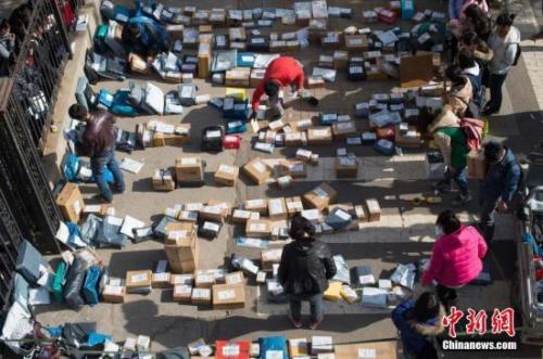 """随着2016年""""双十一""""网购落幕,中国各地迎来快递派送高峰。图为工作人员忙着分拣满地的快递。武俊杰 摄"""
