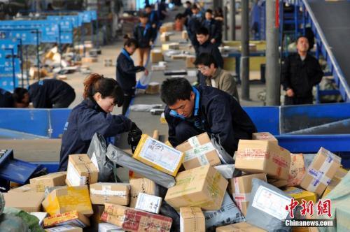 资料图:快递人员正在分拣大量包裹。 <a target='_blank' href='http://www.chinanews.com/'></table>中新社</a>记者 韦亮 摄