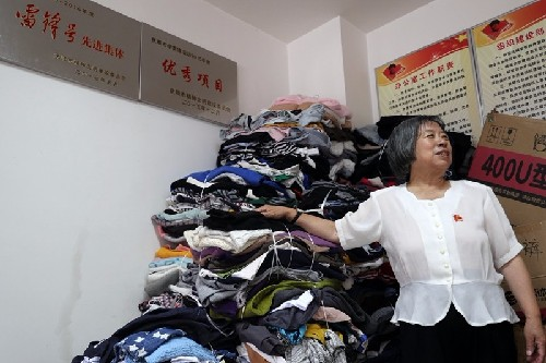 """(44))邓凤兰和其团队回收的衣物将再利用给有用处的人,暂时在办公室堆成""""小山""""-河宁 摄.jpg"""